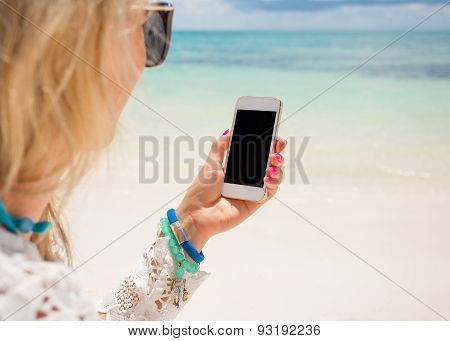 Woman holding smartphone in hand on the beach