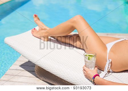 Woman sunbathing by the pool with glass of refreshing cold drink