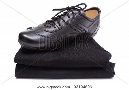 Black Shoes On Stack Of Womanly Clothes. White Background