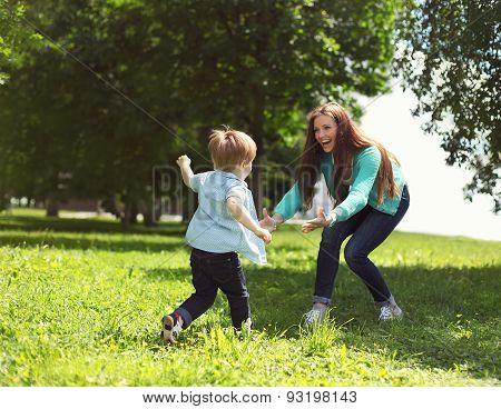Life Moment Of Happy Family! Mother And Son Child Playing Having Fun Together On The Grass In Sunny
