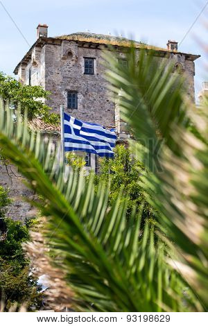 Ouranoupolis Tower On Athos Peninsula In Halkidiki, Flag Of Greece Through The Palm Leaves