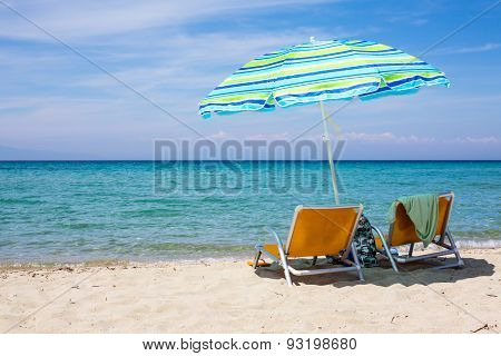 Background With Beach Chairs And Colorful Umbrella On Sandy Beach