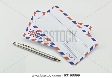 Stack Of Air Mail Envelopes With Pen On White Background