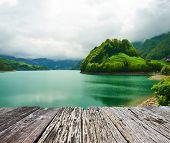 stock photo of emerald  - Beautiful emerald mountain lake in Switzerland under low clouds - JPG