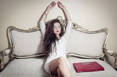 foto of bolivar  - Pretty model girl sitting on victorian sofa posing for camera stretching both hands up and red purse placed on seat next to her - JPG