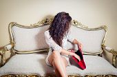 picture of mystique  - Pretty model girl sitting on victorian sofa looking sideways into red purse with hair covering face - JPG