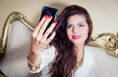 image of mystique  - Pretty model girl sitting on victorian sofa taking a selfie with phone - JPG