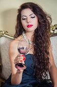 picture of mystique  - Pretty model girl wearing blue dress sitting on victorian sofa holding a wine glass looking into it - JPG