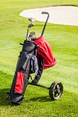 stock photo of golf bag  - a wheeled golf bag full of golf clubs of a vibrant golf course - JPG