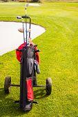 stock photo of golf bag  - a golf bag full of clubs near a sand trap bunker - JPG