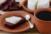 stock photo of juliet  - Brazilian dessert Romeo and Juliet goiabada and Minas cheese with cup of coffee and fresh goiaba on wooden table - JPG