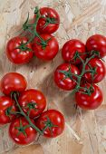 image of cluster  - Fresh tomatoes on a cluster over wooden table - JPG