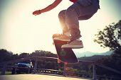 pic of skateboard  - skateboarder legs riding skateboard at skatepark ramp - JPG