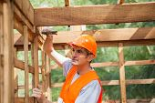stock photo of meter stick  - Male construction worker hammering nail on wooden cabin at site - JPG