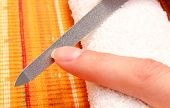 pic of nails  - Woman with file filing nails woman polishing nails manicure nail care - JPG