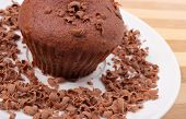 stock photo of chocolate muffin  - Delicious fresh baked chocolate muffin with grated chocolate on white plate lying on wooden cutting board - JPG