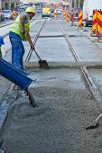 stock photo of concrete pouring  - construction team pouring concrete on a road with boots and protection gear - JPG