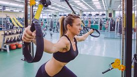 picture of suspension  - Portrait of beautiful woman doing hard suspension training with fitness straps in a fitness center - JPG