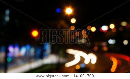 Blurred unfocused lights of cars and motorcycles on road at night in this abstract night shot of city scene.