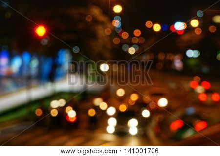 Abstract night shot of city scene. Blurry unfocused lights of cars and motorcycles on road at night.