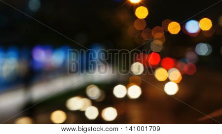 Blurry unfocused lights of cars and motorcycles on road at night. Abstract night shot of city scene.