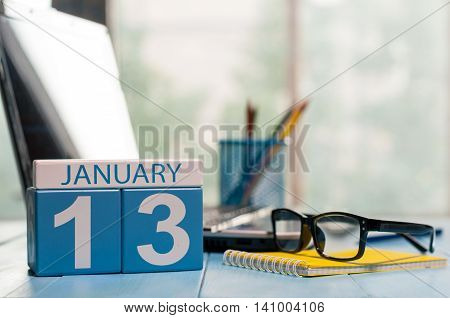 January 13th. Day 13 of month, calendar on designer workplace background. Winter time. Empty space for text.