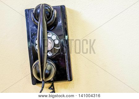 Antique and vintage black telephone hanging on the wall