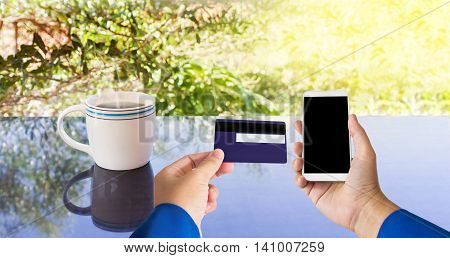 Hand With Credit Or Debit Atm Card And Smart Phone Or Mobile