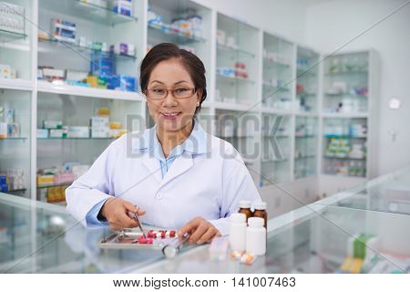 Portrait of Vietnamese pharmacist working with medications in drugstore