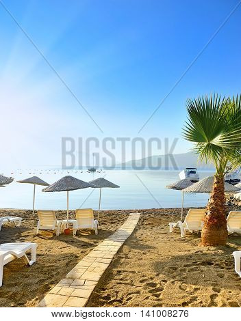 Beach With Sunshades And Sunbeds Against The Backdrop Of The Picturesque Bay Of Blue Sea And Mountai