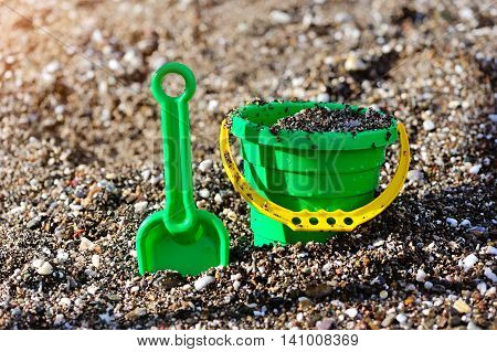 A kids spade and bucket on a pebbled shore