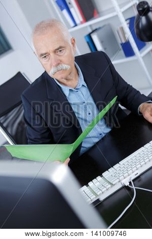 cheerful mature man in formalwear sitting at his working place