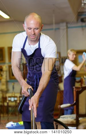 positive professional cleaners team with equipment working at client house