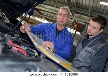 male mechanics working on car engine