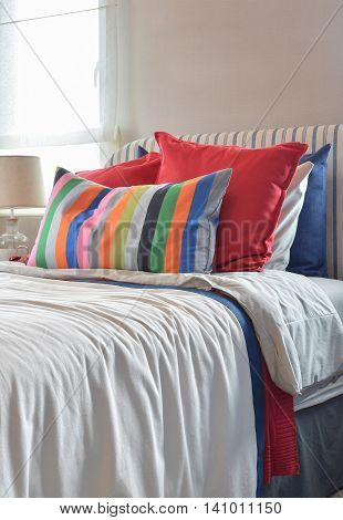 Striped Headboard With Colouful Pillows And Striped Pillow On White Bed Sheet