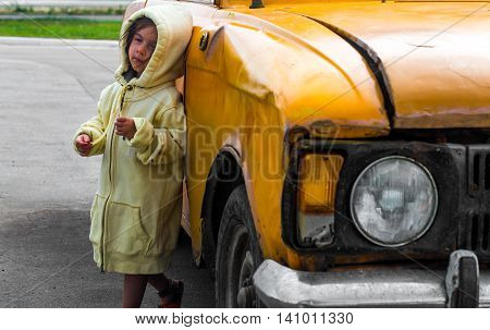 pensive little girl standing near an old wrecked car
