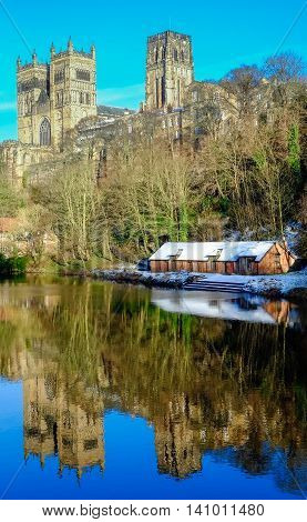 Durham Cathedral looms majestically over the River Wear with a dusting of winter snow. The came water reflects the ancient norman jewel and the riverside boathouse