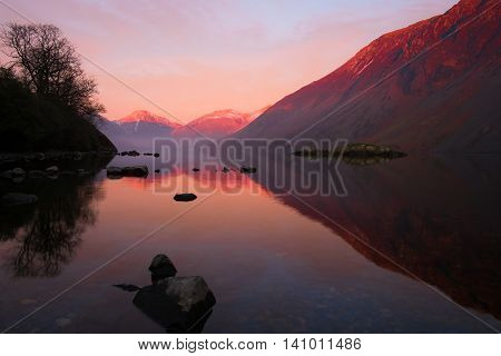 A beautiful aspect across Wastwater in the English Lake District. A view across the still waters towards Wasdale Head and Great Gable, topped with snow and all glowing a lovely pink in the sunset