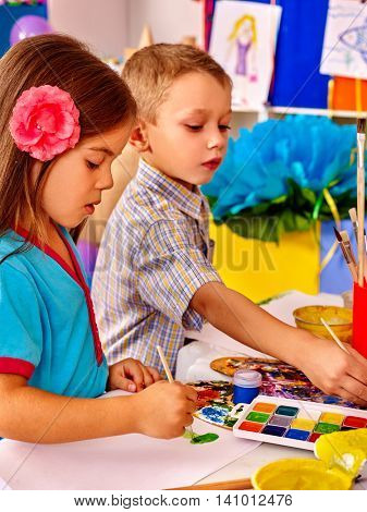Two children girl and boy with brush painting on table in primary school. Painting children lesson in primary school.