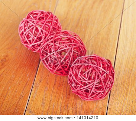red rattan balls lying on wooden background