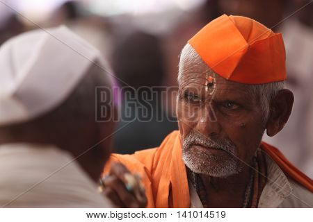 Pune, India - July 11, 2015: An old Indian hindu pilgrim wearing traditional hat in the hindu saffron color.