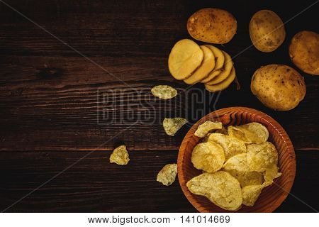 Salty potato chips snack on wood table top view