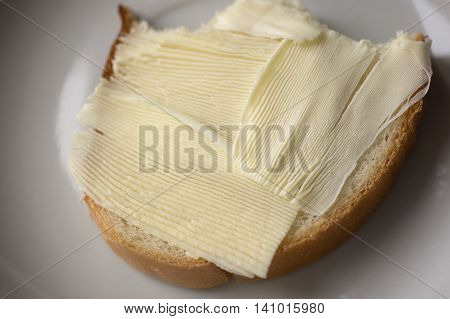 Bitten sandwich with butter on a white plate
