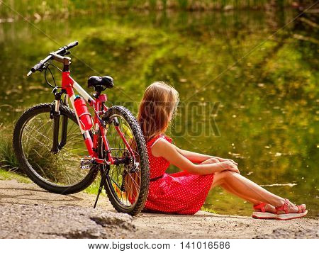 Girl wearing red dress rides bicycle into park. Girl sits leaning bicycle on shore river.
