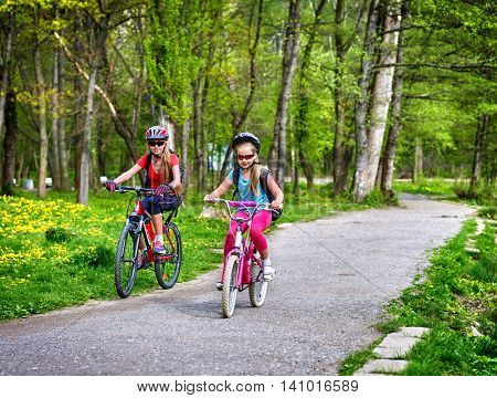 Girls wearing bicycle helmet and glasses with rucksack rides bicycle on asphalt track. Children ride on green grass and flowers in park.