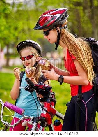 Girls wearing bicycle helmet with rucksack rides bicycle in summer park. Bicycle girls eating ice cream cone .