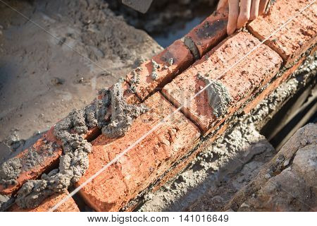 plasterer making up a brick wall with cement