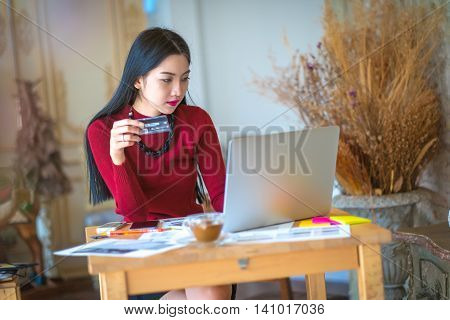 The Cute Young Woman Shopping Online With Her Credit Card And A Notebook Computer At Home