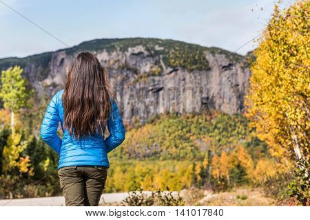 Nature outdoors travel woman mountain lifestyle, unrecognizable brunette hiking girl wearing blue down jacket relaxing looking at view of fall season scenic landscape at park during camping trip.