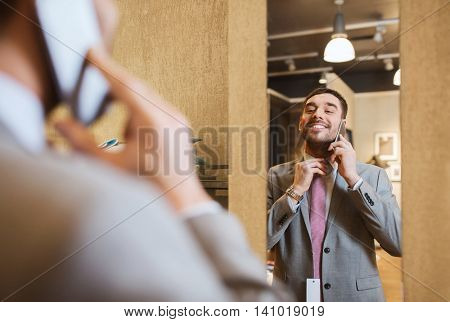 sale, shopping, fashion, style and people concept - happy young man or businessman trying suit and tie on and calling on smartphone at clothing store mirror